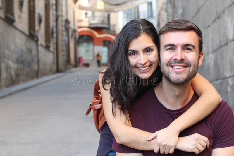 Lyckliga mellan skilda raser par som utomhus ler royaltyfri bild