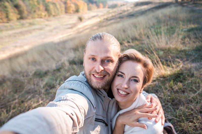 Lyckliga mellersta ålderpar gör selfie utomhus arkivfoto