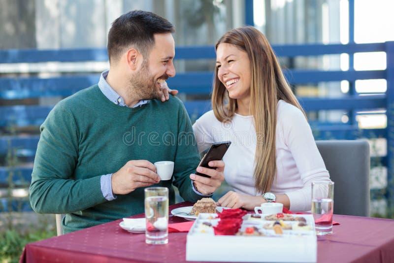 Lyckliga millennial par som firar årsdag eller födelsedag i en restaurang arkivbild