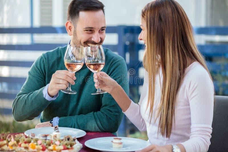 Lyckliga millennial par som firar årsdag eller födelsedag i en restaurang arkivfoto