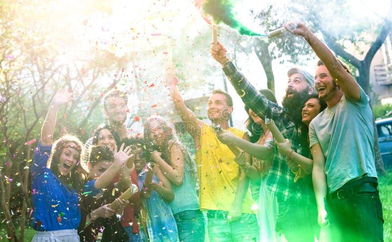 Lyckliga millennial vänner som har gyckel på trädgårdpartiet med mångfärgad rök, bombarderar utanför - ungt millenial fira för st royaltyfria bilder