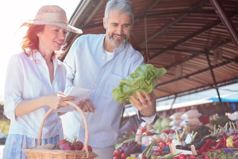 Lyckliga mitt- vuxna par som köper nya organiska grönsaker i en marknadsplats royaltyfri foto
