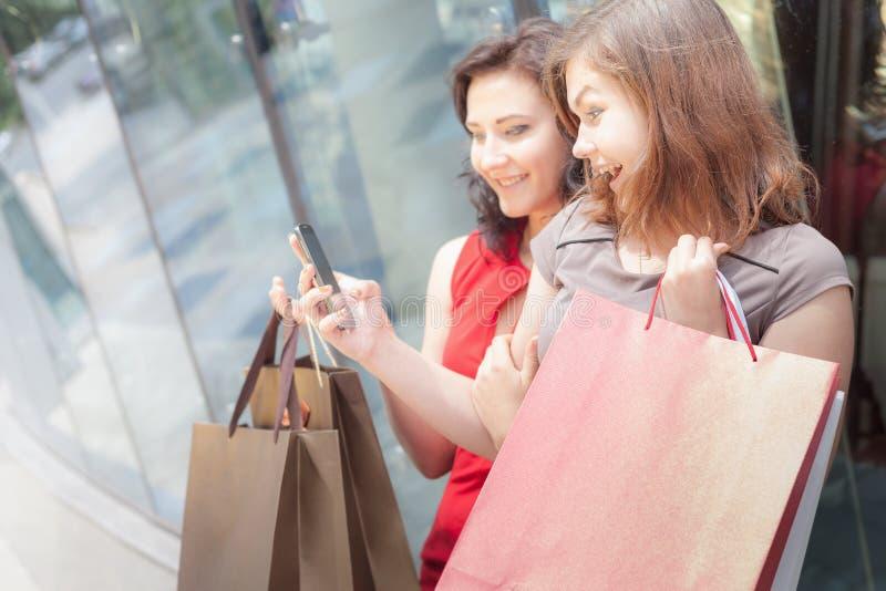 Lyckliga modekvinnor med påsar genom att använda mobiltelefonen, köpcentrum arkivbilder