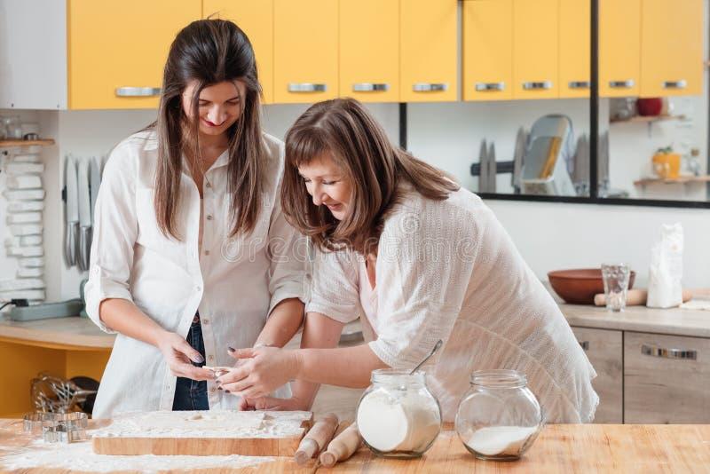 Lyckliga moderdotterkvinnor som bakar kexdeg arkivbild