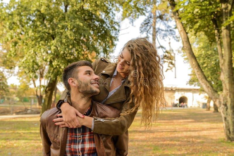 Lyckliga moderna par som har en trevlig tid i det offentligt, parkerar royaltyfri foto