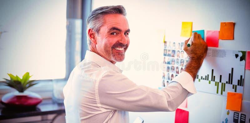 Lyckliga mogna affärsmandanandestrategier på whiteboard i idérikt kontor arkivfoto