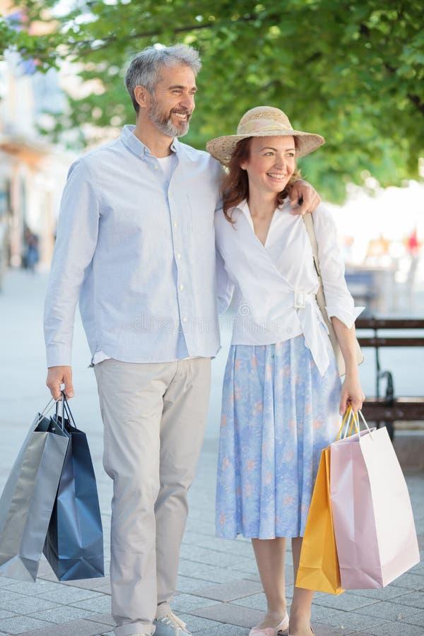 Lyckliga mogna par, make och fru som går tillbaka från shopping royaltyfria bilder