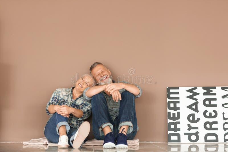 Lyckliga mogna par med tillhörigheter som inomhus sitter på golv flytta sig f?r hus som ?r nytt royaltyfria foton