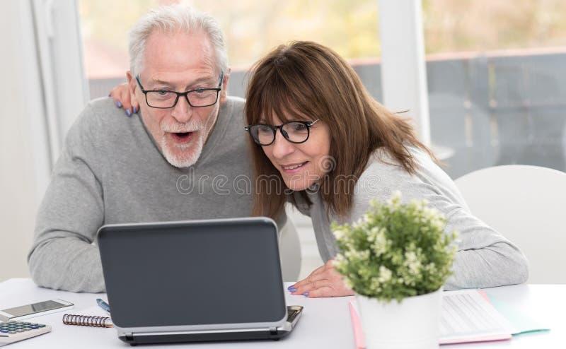 Lyckliga mogna par som har en bra överraskning på bärbara datorn royaltyfria bilder