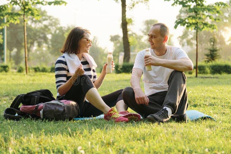 Lyckliga mogna par som sitter i, parkerar på matt kondition och att vila dricka yoghurt efter sportövningar royaltyfria foton