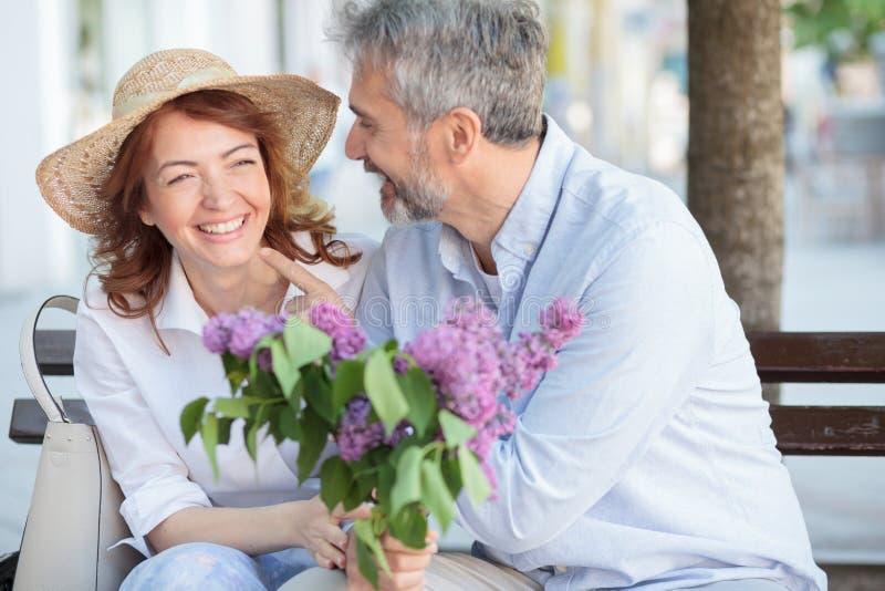Lyckliga mogna par som tillsammans tycker om deras tid och att sitta på en bänk på stadfyrkant arkivfoto