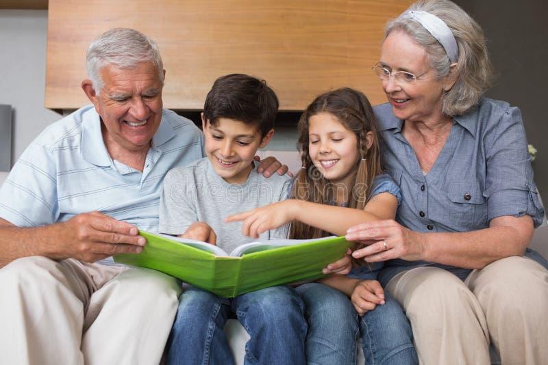 Lyckliga morföräldrar och grandkids som ser albumfotoet royaltyfri fotografi