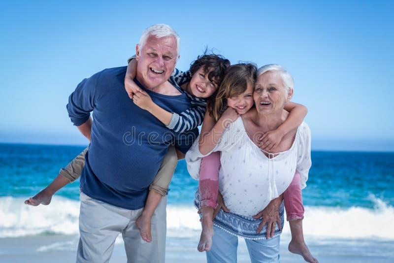 Lyckliga morföräldrar som på ryggen ger sig till barn royaltyfria bilder