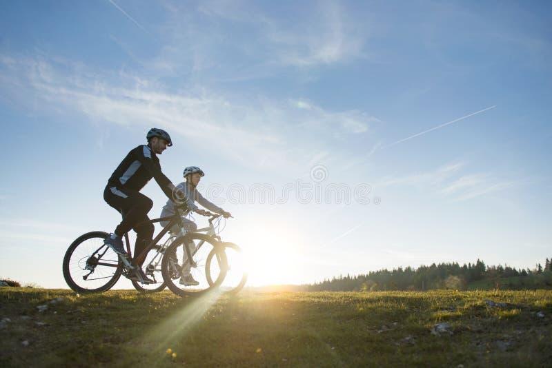 Lyckliga mountainbikepar har utomhus gyckel tillsammans på en sommareftermiddag royaltyfri fotografi