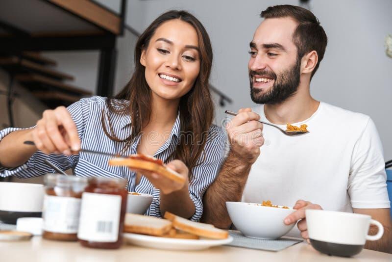 Lyckliga multietniska par som har frukosten royaltyfri fotografi