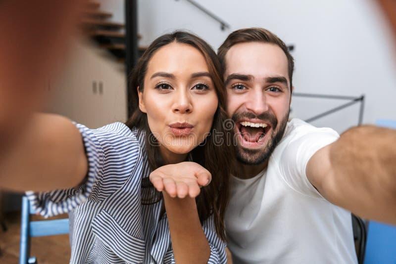 Lyckliga multietniska par som har frukosten arkivfoto
