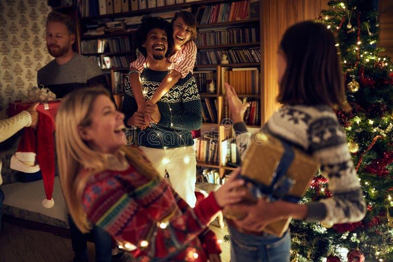 Lyckliga multietniska vänner som tillsammans firar jul royaltyfri foto