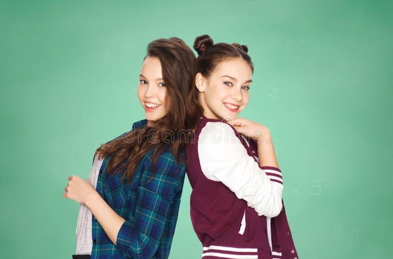Lyckliga nätta tonårs- flickor över grön skolförvaltning arkivfoto