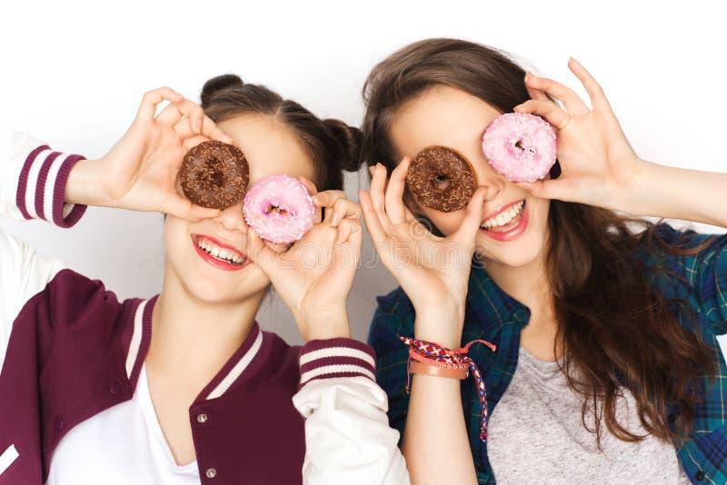 Lyckliga nätta tonårs- flickor med donuts som har gyckel royaltyfria foton