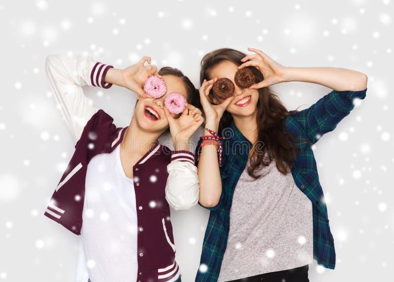 Lyckliga nätta tonårs- flickor med donuts som har gyckel arkivbilder