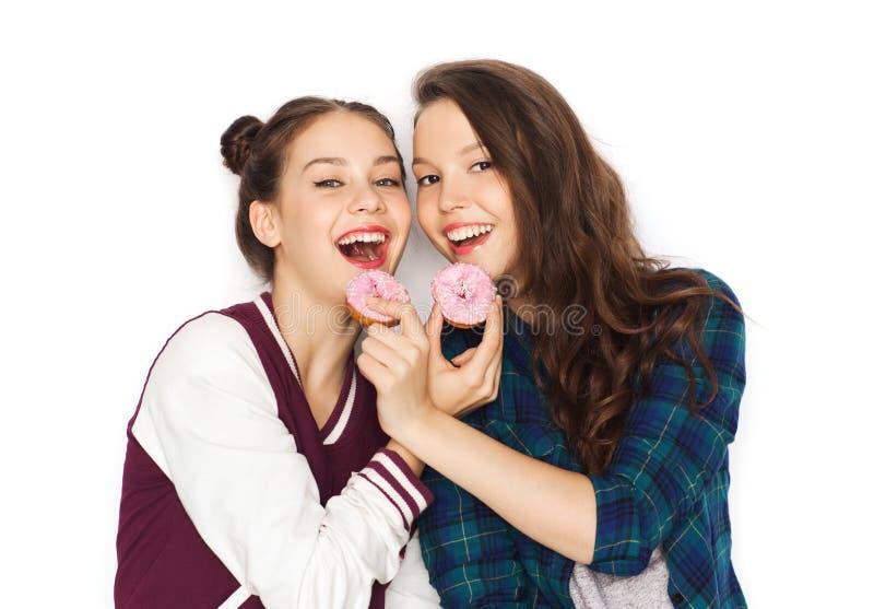 Lyckliga nätta tonårs- flickor som äter donuts arkivfoto
