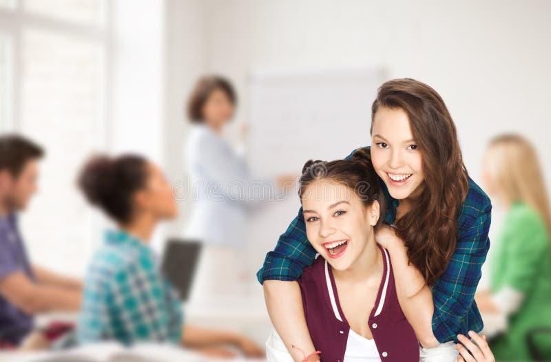 Lyckliga nätta tonårs- flickor som har gyckel på skolan royaltyfri fotografi