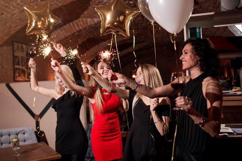 Lyckliga nätta unga kvinnor som rymmer fyrverkeritomtebloss, ballonger, exponeringsglas av vin som firar en ferie i restaurang me arkivbilder