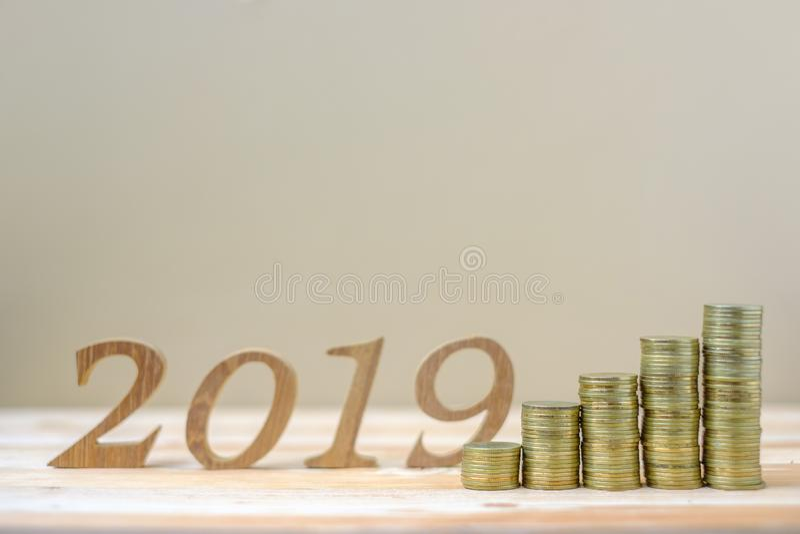 2019 lyckliga nya år med bunten för guld- mynt och tränummer på tabellen affär investering, avgångplanläggning, finans, besparing royaltyfri fotografi