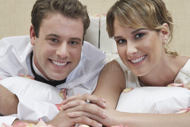 Lyckliga nygift personpar i säng arkivfoto