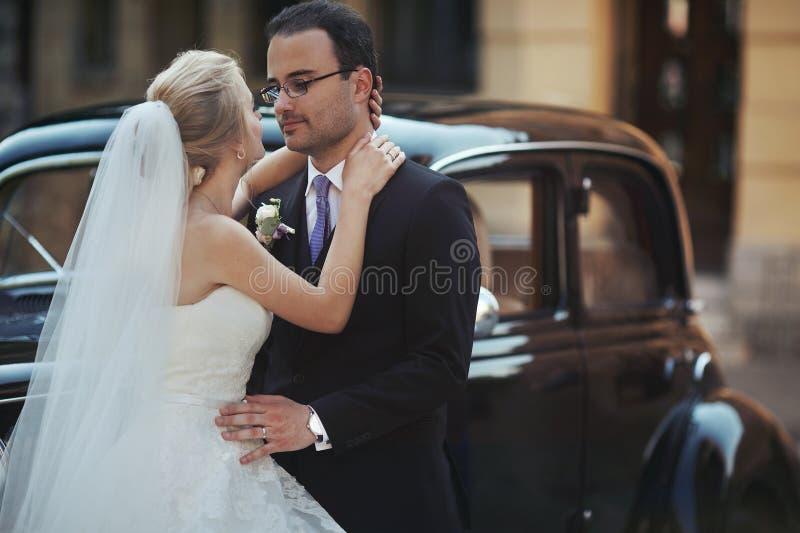 Lyckliga nygift personpar, man och fru som kramar nära stilfullt retro c arkivfoto