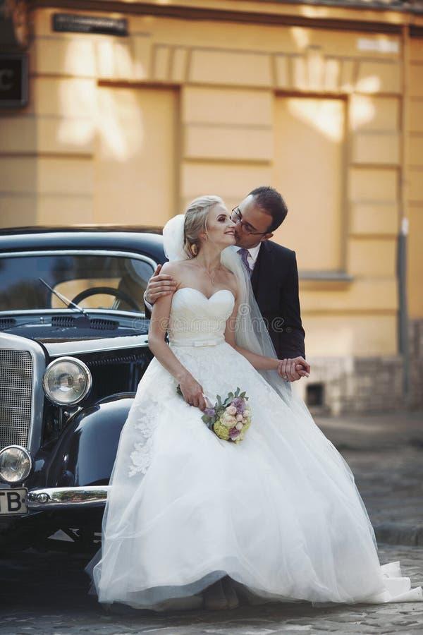 Lyckliga nygift personpar, man och fru som kysser nära stilfullt retro c arkivbilder