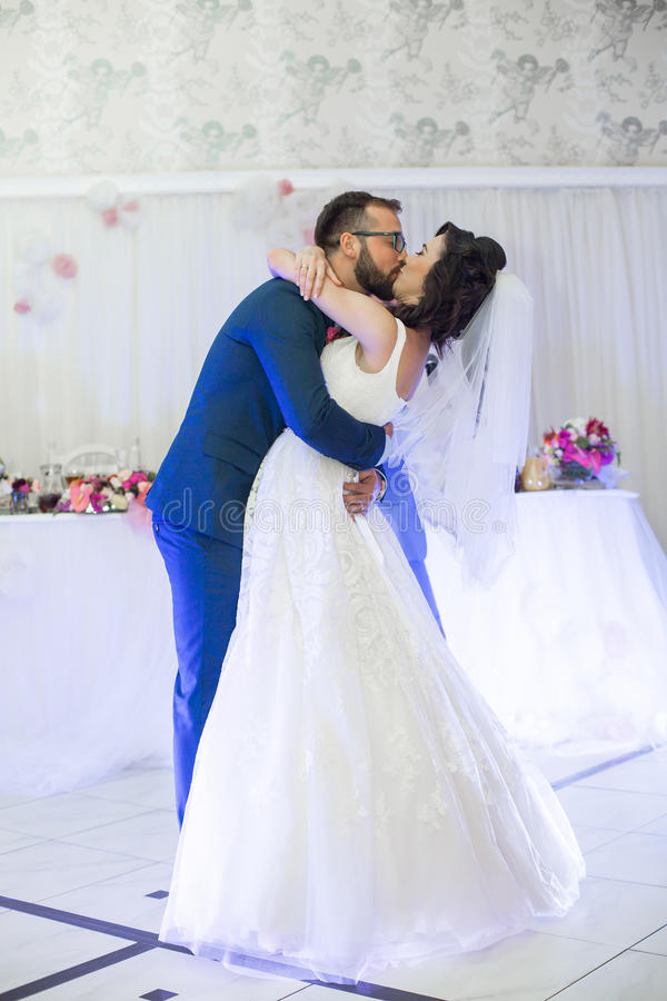 Lyckliga nygift personpar som kysser under deras första dans på weddin royaltyfria bilder
