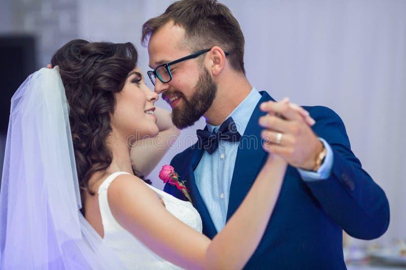Lyckliga nygift personpar som ler på deras första dans på att gifta sig som är beträffande arkivfoton