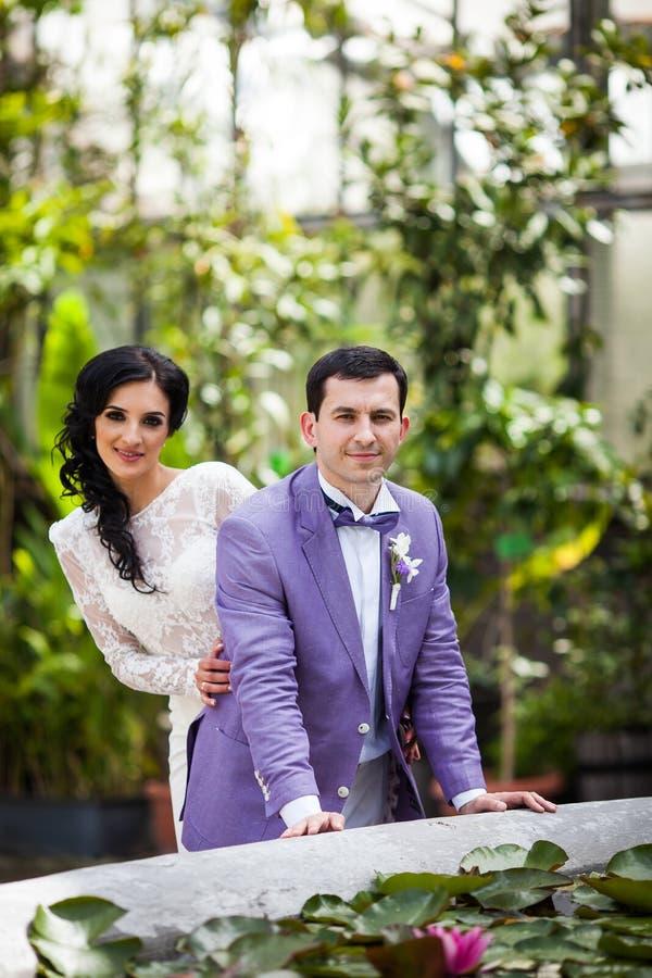Lyckliga nygift personpar som poserar i botaniqueträdgården som förbi omges royaltyfri bild