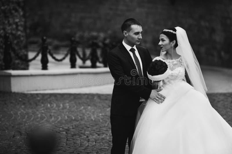 Lyckliga nygift personpar, valentynes som kramar och poserar i ett gammalt royaltyfria foton