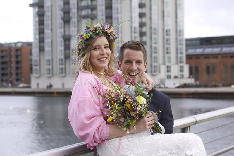 Lyckliga nygifta personer att gifta sig precis gifta sig parpar som ler - flickan med buketten av blommor och den blom- kransen i royaltyfri bild