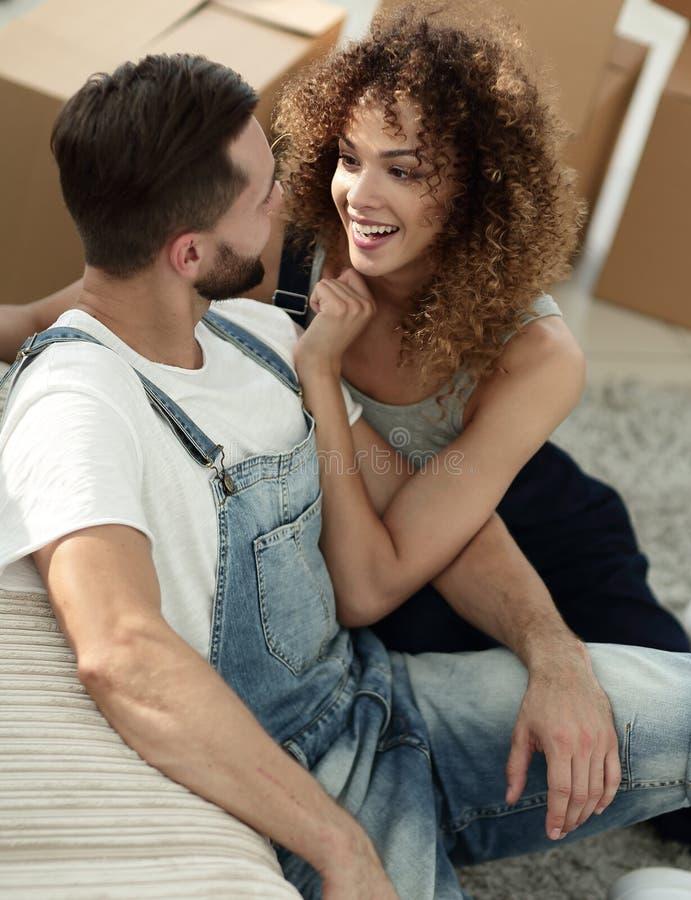 Lyckliga nygifta personer i en ny lägenhet royaltyfri bild