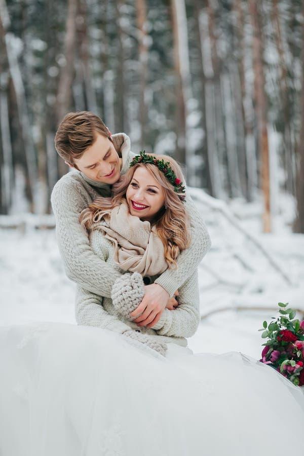 Lyckliga nygifta personer kramar i de förälskade vinterskogparen Vinterbröllopceremoni fotografering för bildbyråer