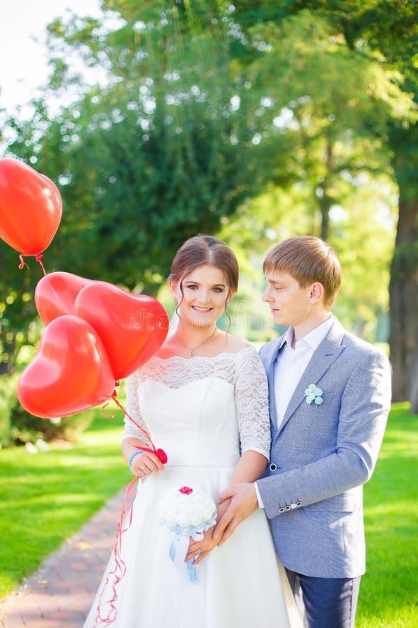 Lyckliga nygifta personer kramar sig på bakgrunden av den härliga naturen arkivfoton