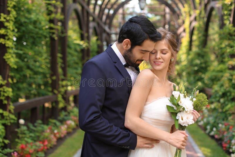 Lyckliga nygifta personer med den härliga gifta sig buketten utomhus royaltyfria foton