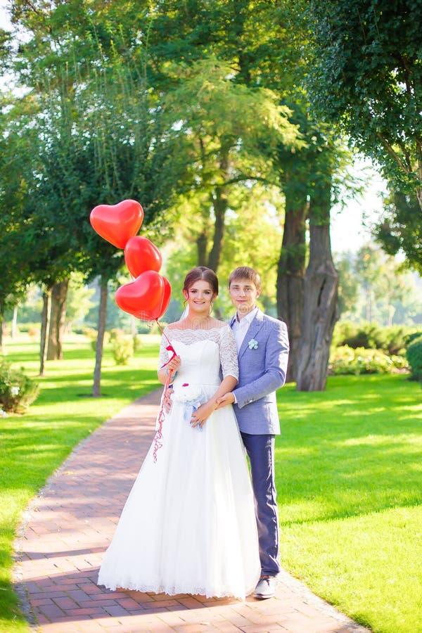 Lyckliga nygifta personer med röda ballonger arkivfoton