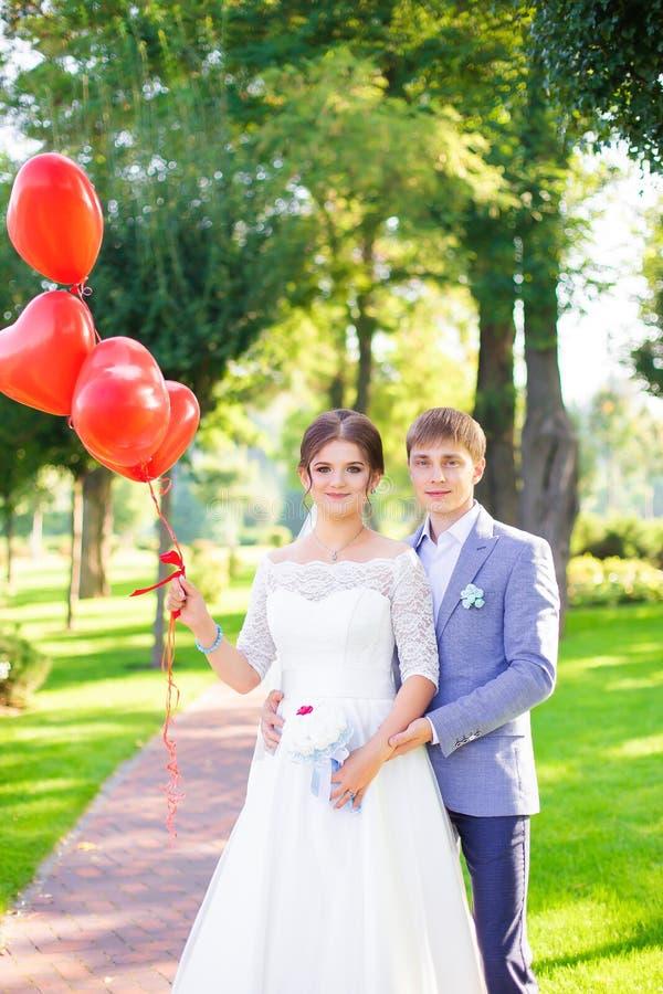 Lyckliga nygifta personer med röda ballonger tätt upp royaltyfri foto