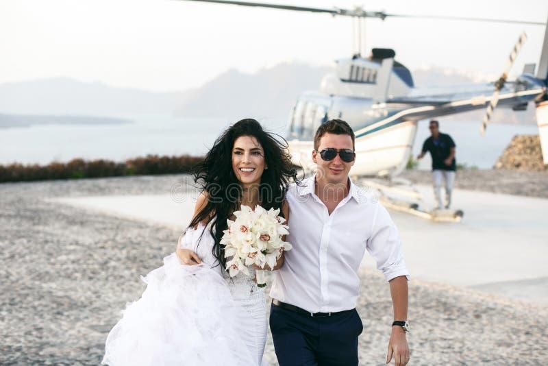 Lyckliga nygifta personer nära helikoptern arkivfoton