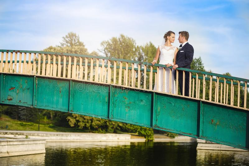 Lyckliga nygifta personer på bron parkerar in arkivfoton