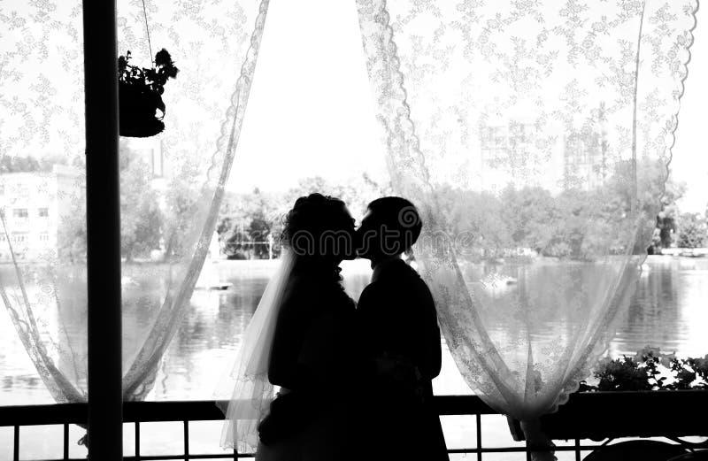 Lyckliga nygifta personer som inomhus kysser Den brunettbruden och brudgummen står near fönsterkonturer av lyckligt arkivbilder