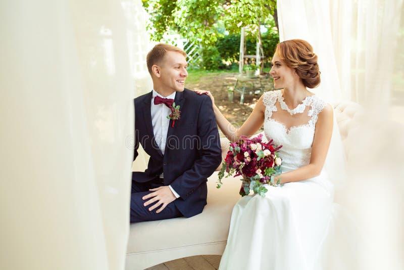 Lyckliga nygifta personer som ser de och sitter på den beigea soffan royaltyfri foto
