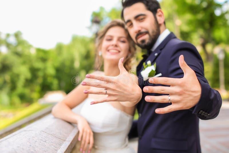 Lyckliga nygifta personer som utomhus visar deras vigselringar arkivfoton