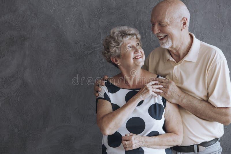 Lyckliga och älskvärda höga par mot betongväggen med kopia s royaltyfri bild