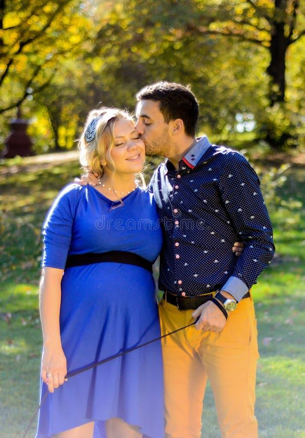 Lyckliga och för barn gravida par som kramar i natur arkivbild