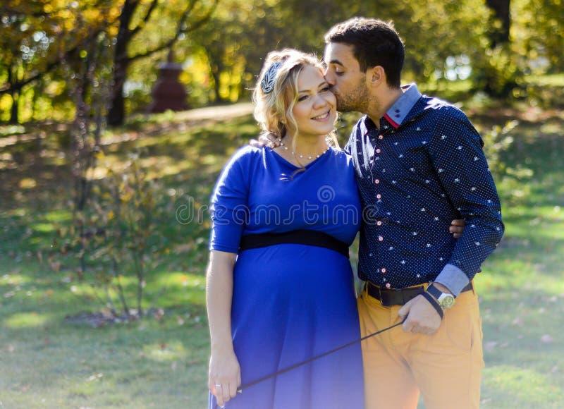 Lyckliga och för barn gravida par som kramar i natur royaltyfria bilder